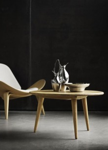 The Shell Chair and the three-legged coffee table CH008. Both designed by Hans J. Wegner in 1963 and 1954 respectively.