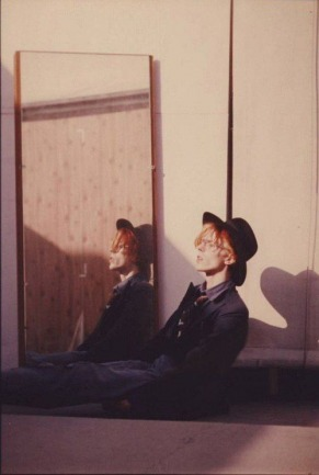David Bowie sitting on fllor mirror